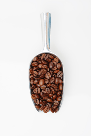 coffee beans in metal scoop on white, top view