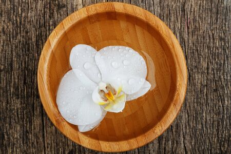 White orchid floating in bamboo bowl on wooden background. Top view.  Фото со стока
