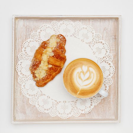 Latte art coffee and croissant on white