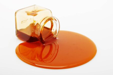 Honey spill from a glass jar on white