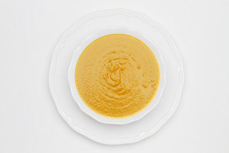 Plate of pea cream soup on white background. Top view