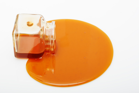 Honey spill from a glass jar on white background