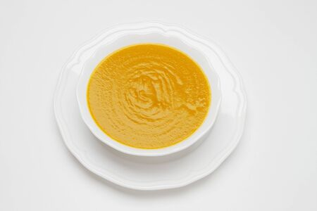 Plate of pea cream soup on white background