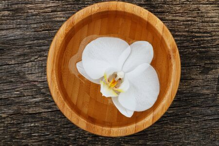 White orchid, phalaenopsis flower in bamboo bowl on wooden background. Top view. Фото со стока