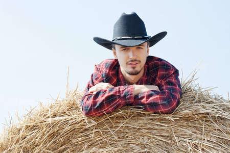 young cowboy on haystack