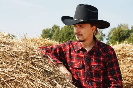 young cowboy leaning on a haystack Фото со стока