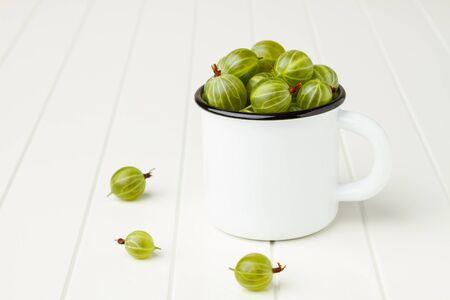 Fresh green gooseberries in an enamel mug on white table