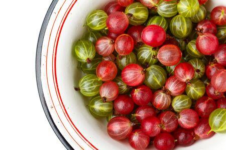 Fresh gooseberries in an enamel bowl on white background. Top view Фото со стока