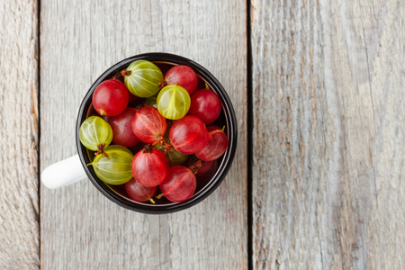 Fresh green and red gooseberries in an enamel mug on wooden table. Top view Фото со стока