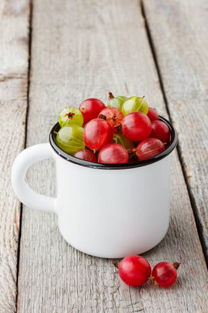 Fresh green and red gooseberries in an enamel mug on wooden table.