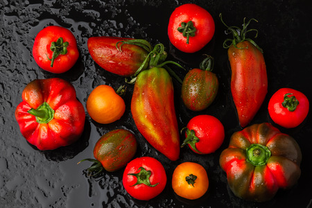 Fresh tomatoes and peppers on a black background. Top view