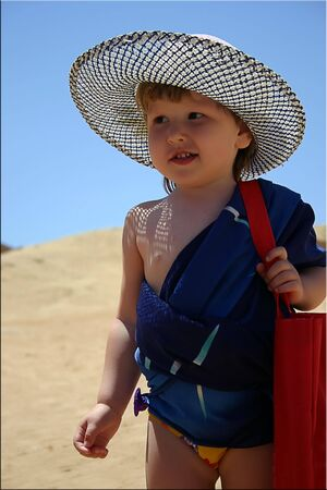 Little girl in panama on the beach with red bag and blue scarf around the body Stock Photo - 925113
