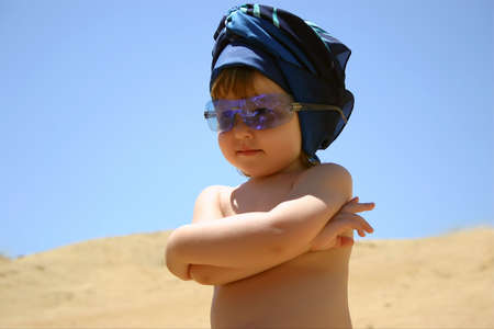 sunnies: Little girl in blue sunglasses & hadscarf standing on the beach with crossed hands on her chest Stock Photo