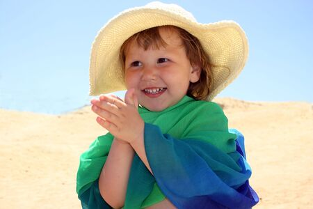 Little girl in straw & green-blue scarf is clapping her hands and laughting, seems to be very happy Stock Photo - 925119