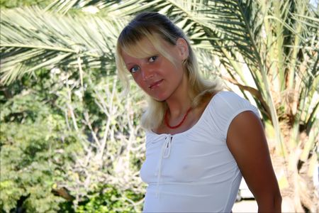 suntanned: Beautiful suntanned blond girl with red coral necklace in white blouse & differend colored eyes