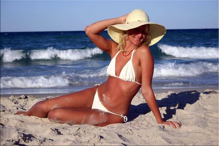 smilimg beautiful suntanned blonde in white bikini & straw on the sand near the sea
