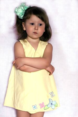 sad glamour little girl with green bow wearing yellow dress with flowers Stock Photo - 920457