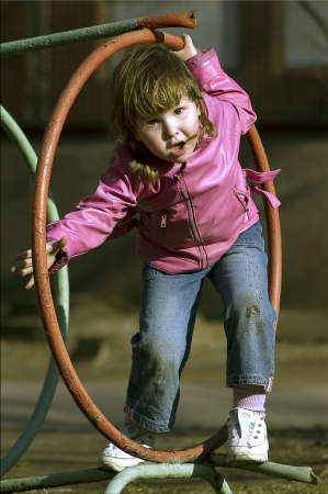 Little girl playing outdoor within circle in pink coat & blue jeans Stock Photo - 925138