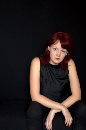 seemed: Red-hair pretty young woman in black closes on black background seemed to be sad Stock Photo