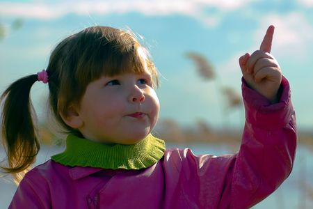 Little girl in pink coat pointing in the sky on the sky and river background photo
