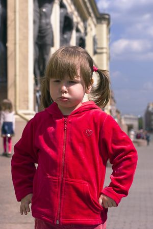 Unhappy girl in red closes in old sity street Stock Photo - 942725