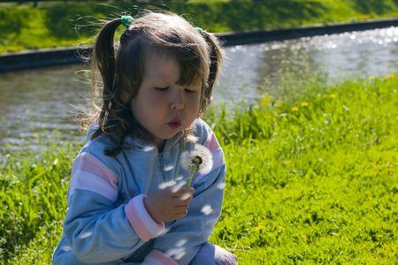 Little girl blowing out dandelion's seeds over river background Stock Photo - 945076