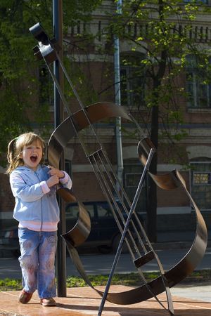 Little girl is Singing near fake contrabass outdoors