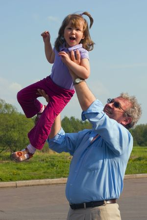 above head: Grandfather is making granddaughter Jumping in the sky, holding her hight above head