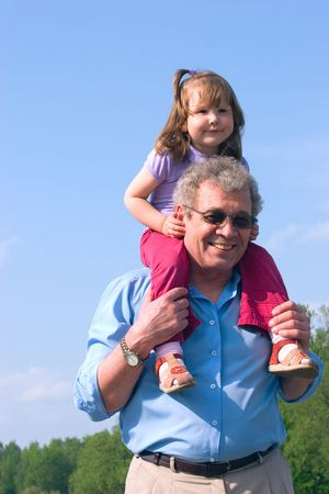 Happy granddad with granddaughter on his shoulders over skies and forest background photo