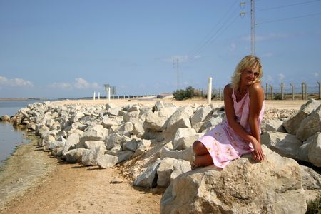 Blonde in pinl closes is sitting near road and water on rock photo