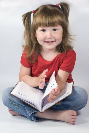 Little Girl with ponytails is holding a day planner, studio photo