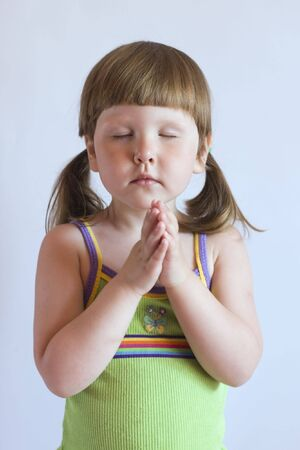 faithfulness: Praying little girl in green top with ponytails, studio