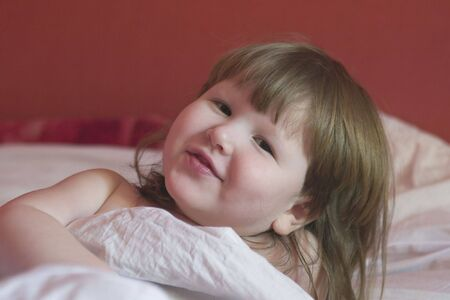 little girl is waking up, looking at you and smiling photo