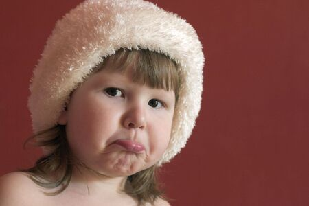 Sad little girl in white hat over red background Stock Photo - 1117330