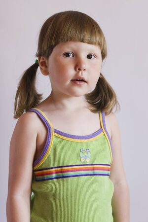 ponytails: Interested little girl with ponytails in green top Stock Photo