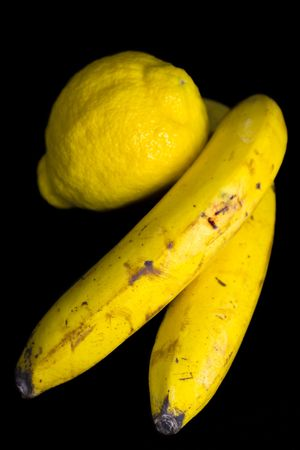 sours: Two ripe yellow bananas and lemon over black background, isolated