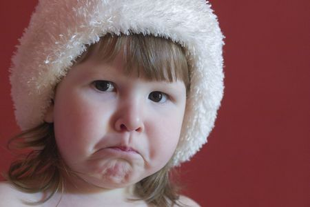 Upset little girl in white hat over red background Stock Photo - 1229834