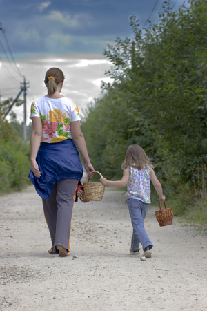 Mother and daughter are walking far away on rural road in cloudy summer day