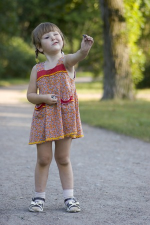 appreciating: Little girl in the park wearing dress appreciating whe stone she holding in her hand Stock Photo