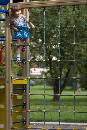 climbed: Little girl wearing blue-white spotted dresson playground climbed high Stock Photo