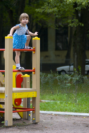 Little girl wearing blue-white summer dress is playing pretty high on playground Stock Photo - 1518386