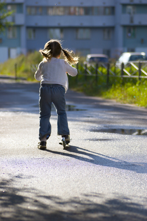 ponytails: Little girl with blond ponytails wearing white sweater and jeans riding scooter in sunset lights, back view
