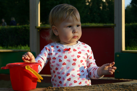 Little girl in sandbox looking away in sunset lights photo