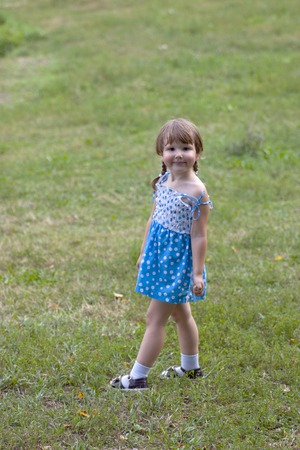 Smiling little cutie standing on the grass and looking back at you Stock Photo - 1518396