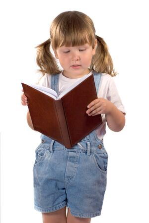 freetime: Little girl with ponytails wearing blank t-shirt and jeans is reading a book isolated on white