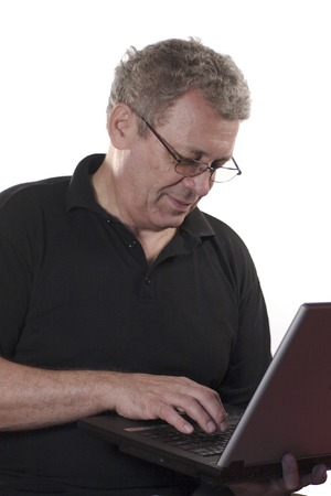Senior man wearing black shirt and glasses answering on e-mail from laptop isolated on white photo