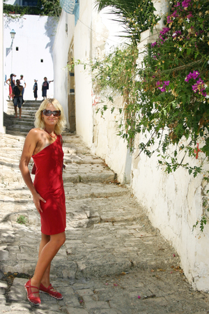 Beautiful tourist wearing sunglasses and kittle red dress in medina of Tunisia photo