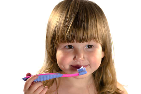 exemplary: Little irl with blond hair going to clean teeth isolated on white Stock Photo