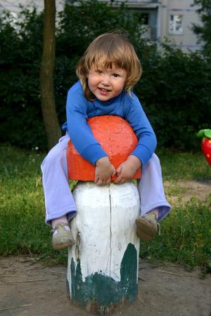 Girl on playground climbering on huge mushroom in sunset lights Stock Photo - 1674863