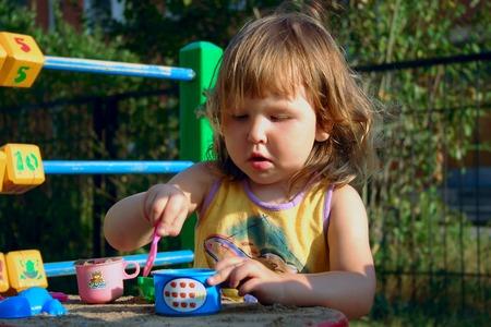 Little girl playing in sandbox in bright sun lights photo